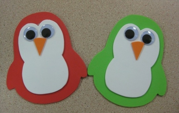 diys for your room, two penguins made from red and green felt, decorated with white nd orange felt details, and stick on eyes