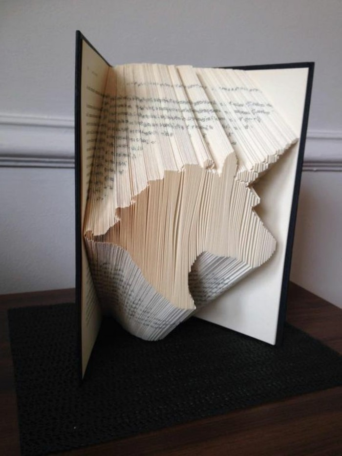 a unicorn head, made from folded pages, inside an open book, with dark hard covers