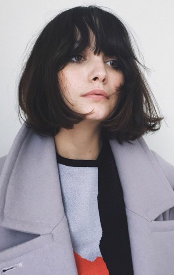 cute short haircuts, woman with messy black, chin-length hair and bangs, wearing big grey woolen coat, and colorful sweater