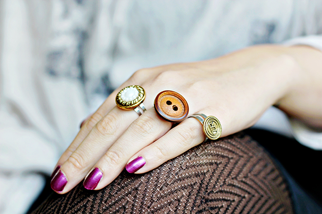 woamn's hand, with shiny purple nail polish, easy arts and crafts, three rings, made from clothes buttons