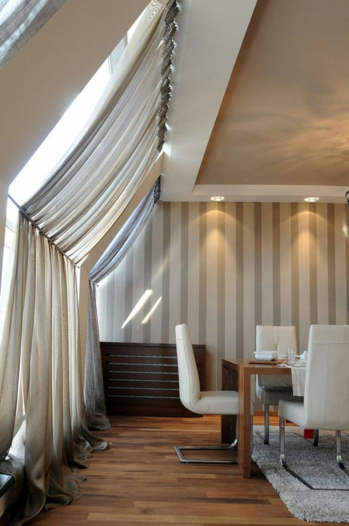 curtain ideas, dining room with large sloping windows, pale cream curtains, held with metal rod, wooden table with white leather chairs