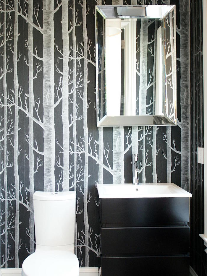 bathroom remodeling, dark wallpaper decorated with light grey painted leafless trees, modern white toilet seat, and a black chest of drawers with a white sink