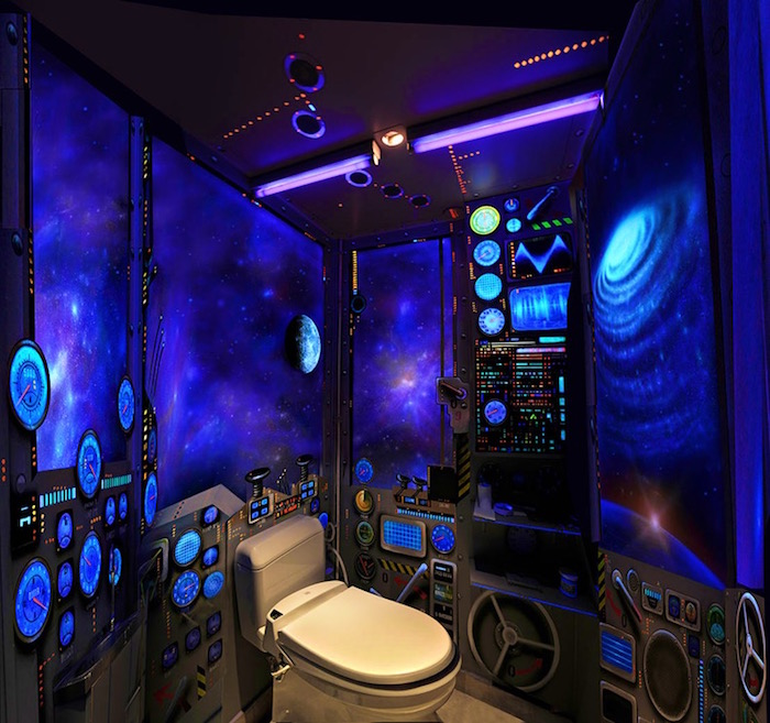 bathroom remodel, small toilet painted to look like a spaceship, dark blue walls, with murals of galaxies and stars, small flickering lights, various painted switches and machinery