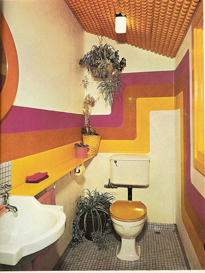 retro 1960's toilet, grey mosaic floor, white retro sink, toilet seat with wooden cover, walls with pink, orange and yellow bending stripes, several potted plants, orange textured ceiling
