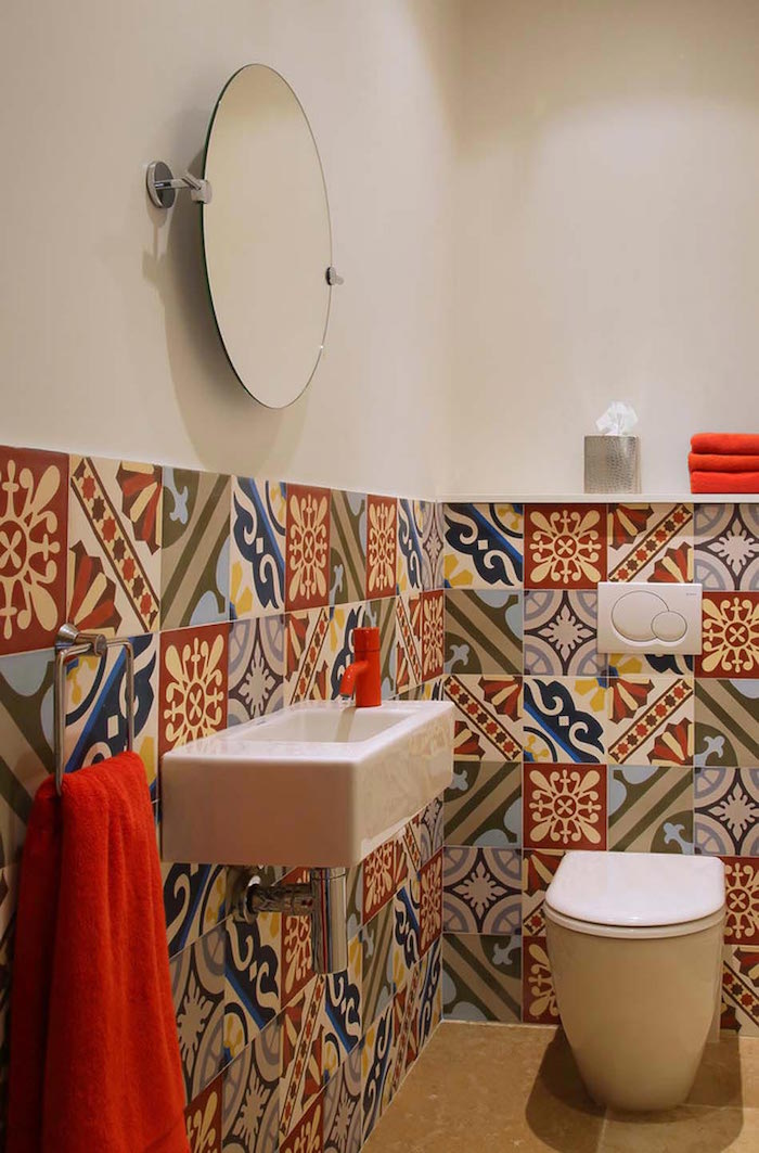 bathroom decorating ideas, bathroom with modern white toilet seat, and rectangular sink, red water tap and towels, upper half of the walls is plain white, lower part is decorated by multicolored, patterned and mismatched tiles