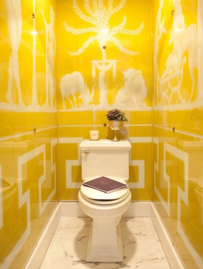 bathroom remodeling, narrow toilet with vintage white toilet seat, with flower vase, book and candle, walls covered with yellow panels, containing white drawings in Ancient Roman style