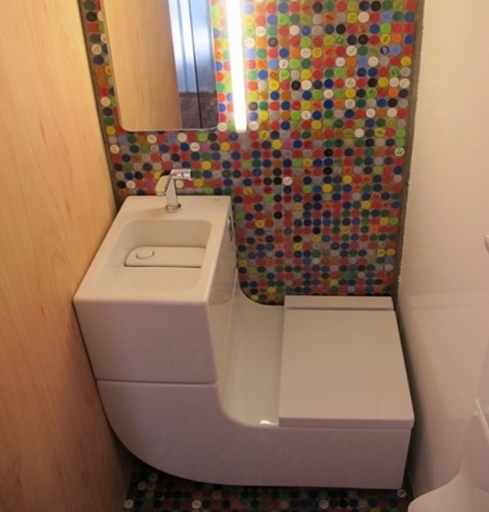 bathroom remodeling, small space with white sink, and toilet seat all in one, one wall is covered in pale wooden board, one is white, and one is decorated with multicolored mosaic, with mirror and light