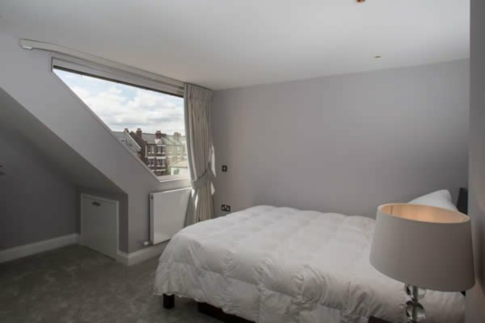 bedroom curtains, plain attic bedroom, with pale grey walls, asymmetrical window with off-white curtain, bed and night lamp