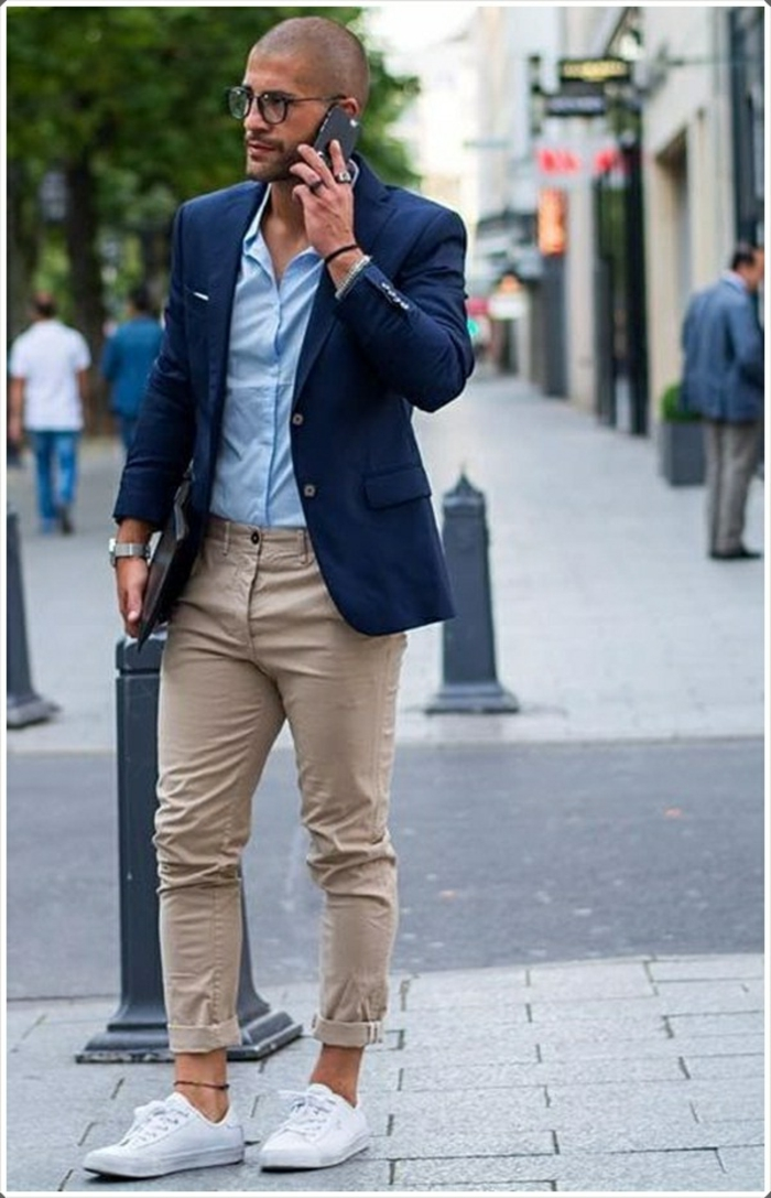 beige carrot pants, combined with white sneakers, and an ankle bracelet, worn by man in dark navy blazer, over pale blue shirt, business casual dress code