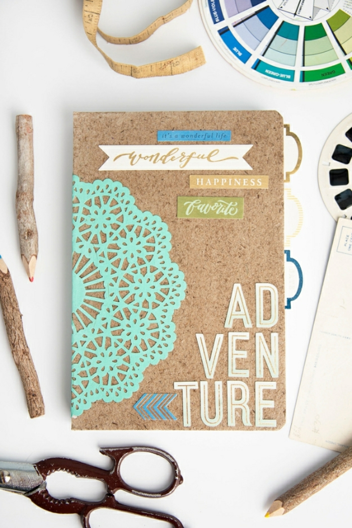 journal with cork cover, decorated with cutouts, paper letters and a pale blue doily, diy craft projects, pencils made of rough wood and, other small items