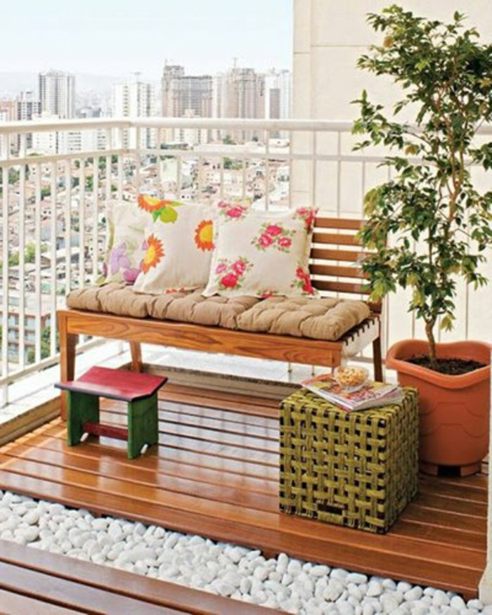wooden bench with beige cover, and three floral cushions, porch ideas, wooden floor with white pebbles underneath, potted plant and small chair