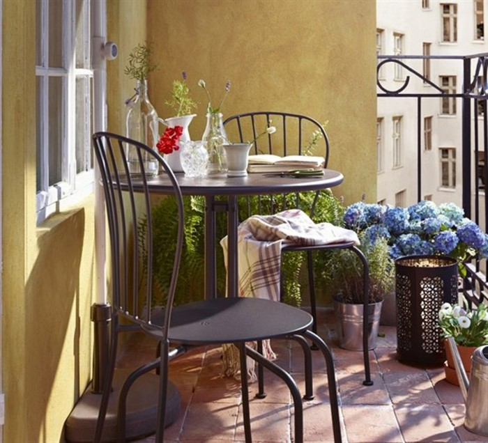 black round table with two matching chairs, near yellow wall, potted plants and black railing, porch décor