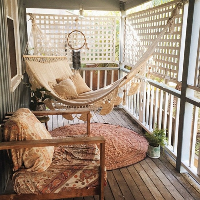 pale beige hammock, with crochet details and pillows, hanging over round oriental rug, near wooden chair with cover and dreamcatcher, covered patio ideas