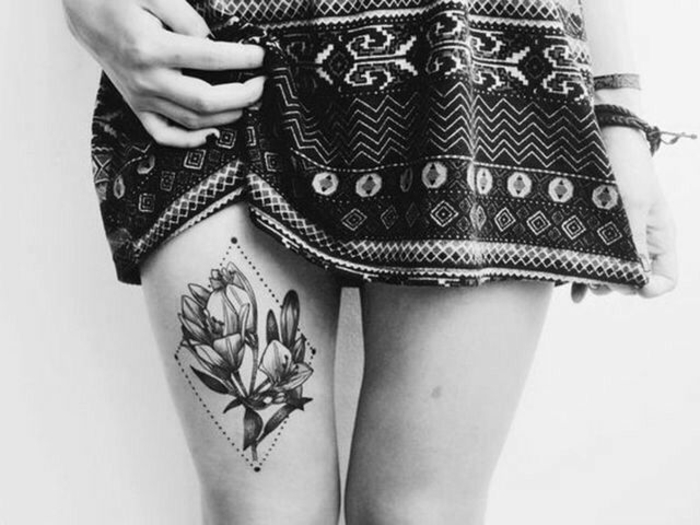 woman with short, patterned skirt, with an image of two crocuses, inside a dotted diamond-shape, tattooed above her knee