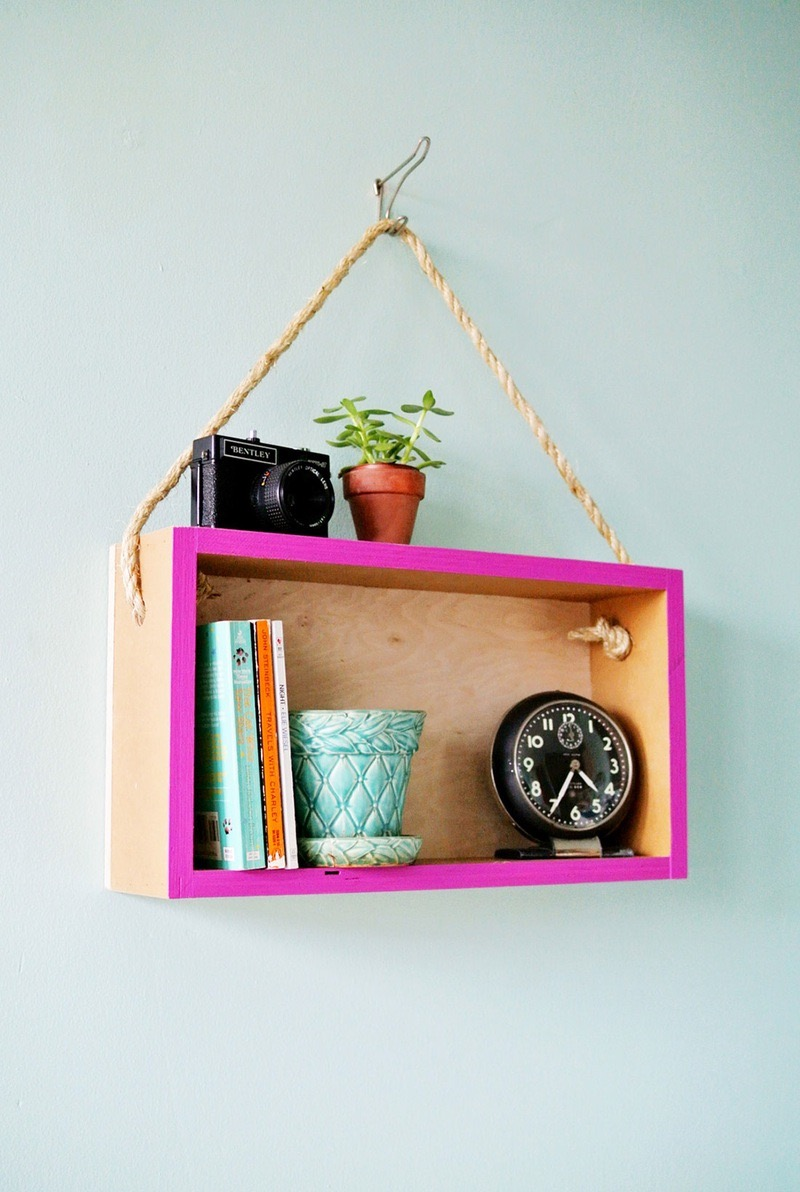 wooden box hanging on thick rope, painted in pale orange, and vivid purple, and containing books and other items
