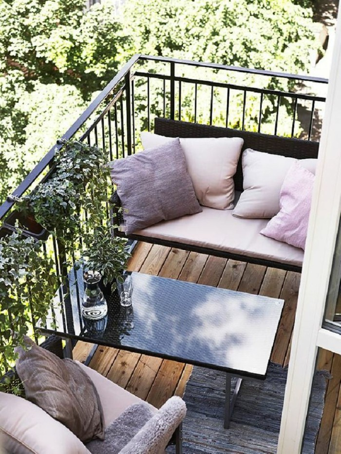 tiny terrace with black metal railing, with brown and pink settee and matching chair, both decorated with pink cushions, front porch decorating ideas, black rectangular table and rug