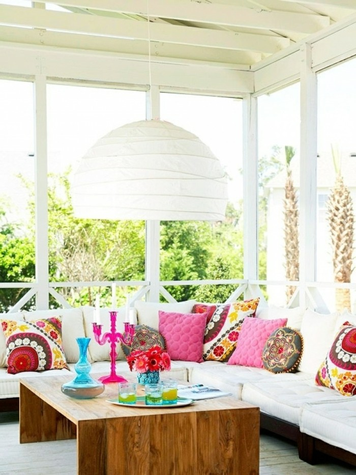 covered patio ideas, wooden table with many, bright colored decorative objects, large white and brown corner sofa, with many cushions in different shapes and colors, large white chandelier
