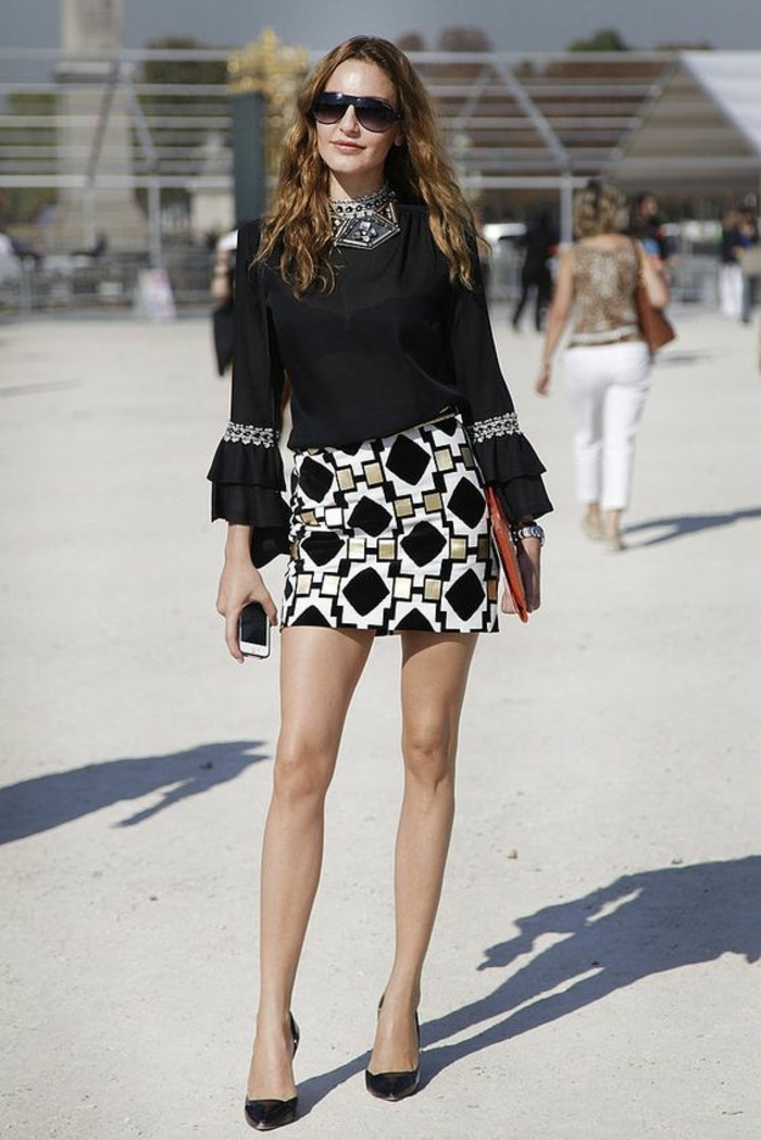 dress attire, slim brunette woman, wearing black top, with embellished and embroidered details, and black white and gold mini skirt, with geometrical pattern