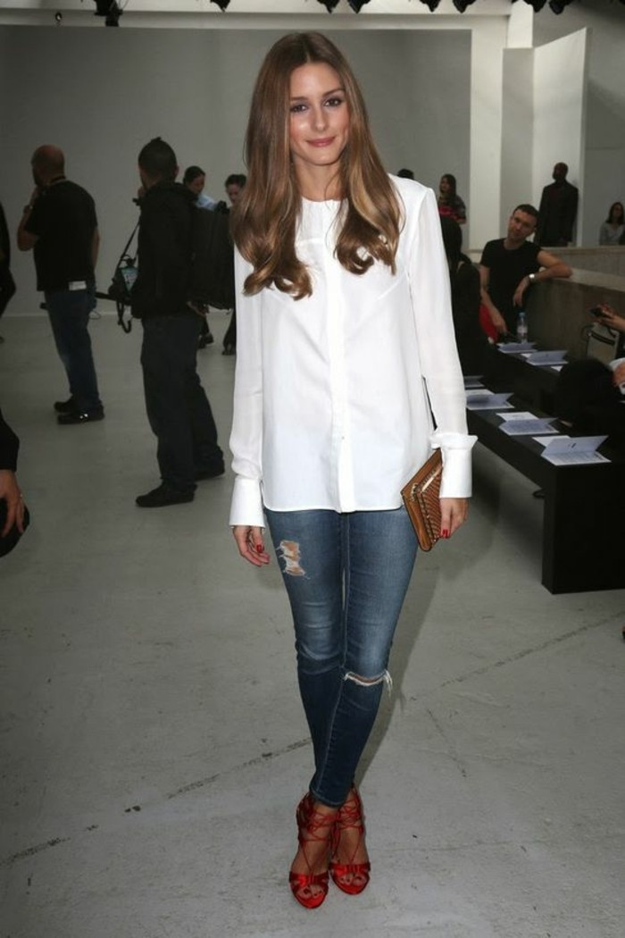 business casual for young women, smiling brunette with wavy hair, wearing white shirt with small frills, dark blue ripped jeans, and red satin heels with straps