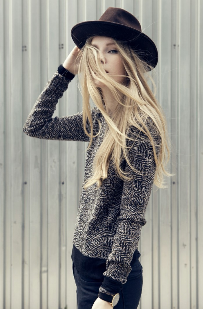 casual clothes, slim young woman with long blonde hair, wearing black and white patterned sweater, black skinny trousers, and a dark maroon felt hat