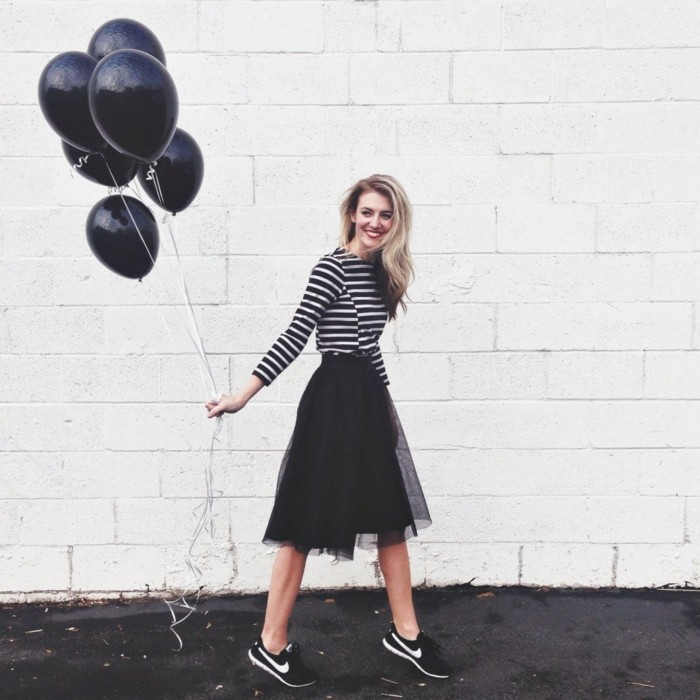 casual clothes, smiling woman with black and white striped top, black tulle skirt, and black and white sneakers, holding six black balloons