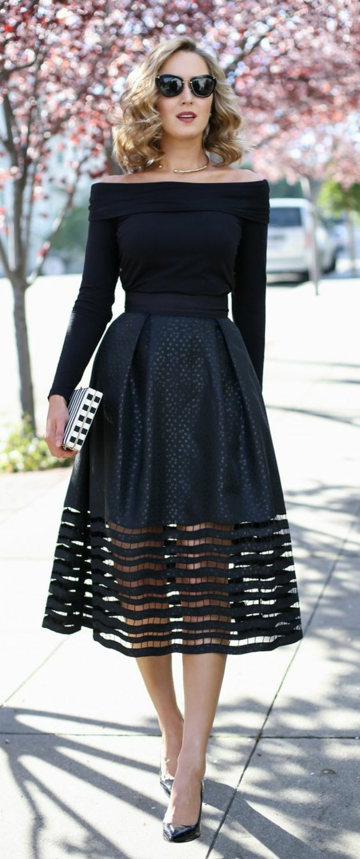 dress attire, blonde woman with shoulder-length curly hair and sunglasses, wearing black off-shoulder sweater, and black embellished skirt, with thick see-through lace hem