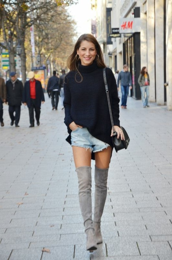 casual dress code, oversized black turtleneck sweater, distressed pale denim shorts, and grey suede over-the-knee boots, worn by smiling brunette woman