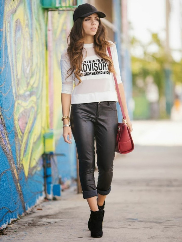cute work outfits, brunette woman with wavy hair, wearing black leather ankle trousers, white t-shirt with print, black ankle boots, and black baseball cap, with coral red shoulder bag