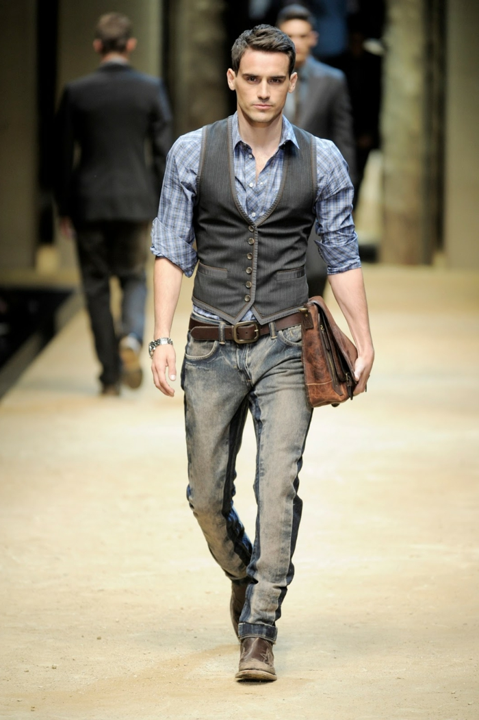 male catwalk model, wearing pale blue chequered shirt, grey button up vest, distressed cowboy jeans, and worn vintage shoes, casual clothes for men, antique looking suede bag in his hand