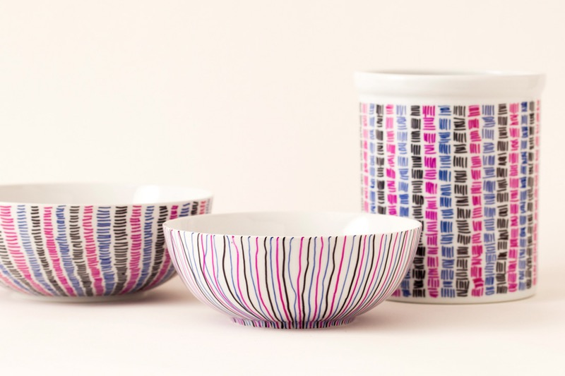 two white ceramic bowls, and a mug, decorated with lines, and tiny scribbles, in pink blue and black