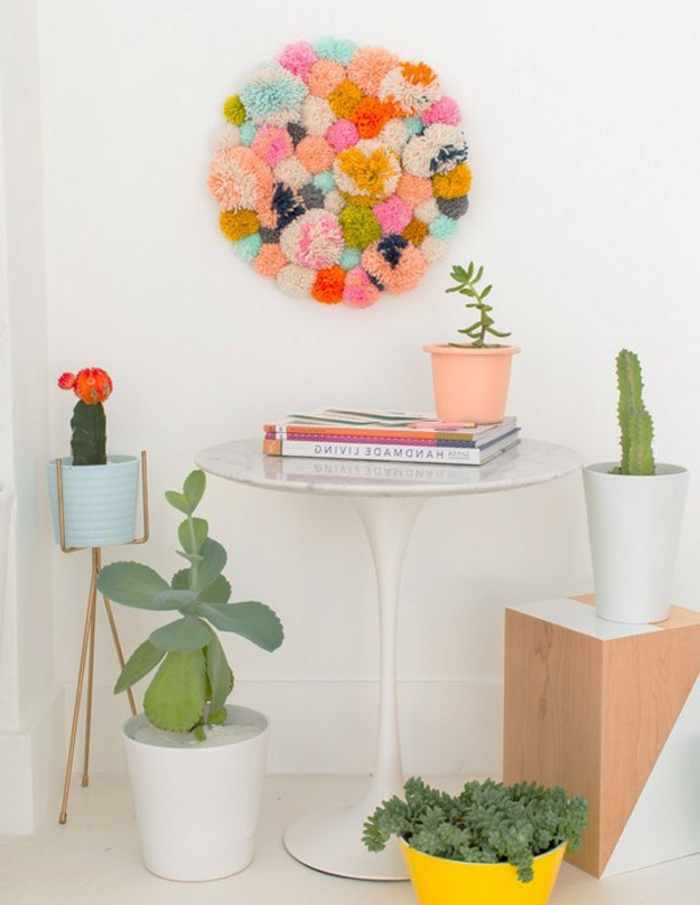 round wall decoration, made from multicolored pom-poms stuck together, easy arts and crafts, hanging over a small white table, with wooden stool, and potted plants