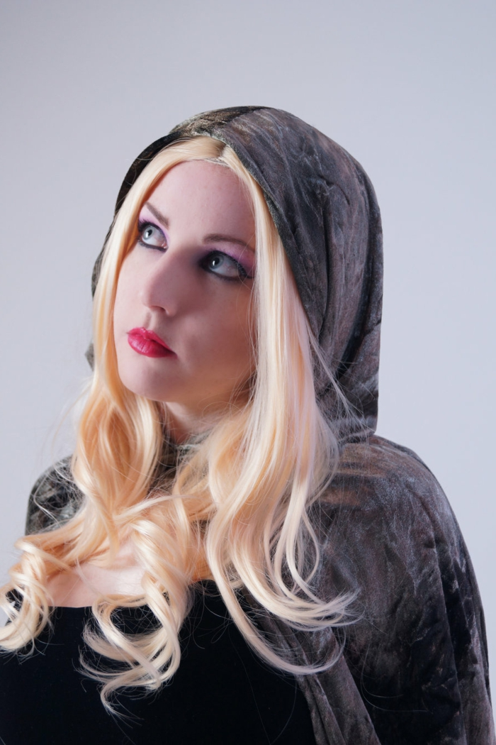 woman with red lipstick, black eye-make-up and blonde wig, wearing a black top, and dark grey velvet cape and hood