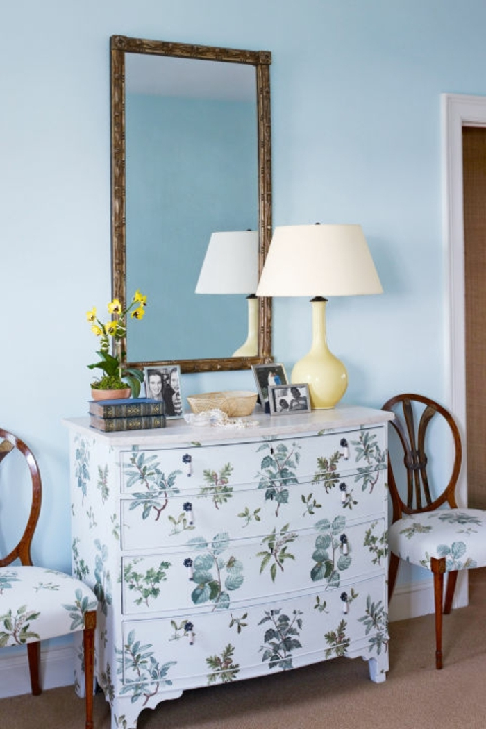 white chest of drawers, decorated with green plants decoupage, near two chairs with similar pattern, diy craft projects, large mirror and lamp