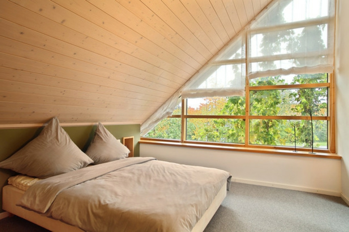 bedroom with sloped ceiling, covered with wooden planks, asymmetrical window with short, sheer asymmetrical curtain, pale brown bed