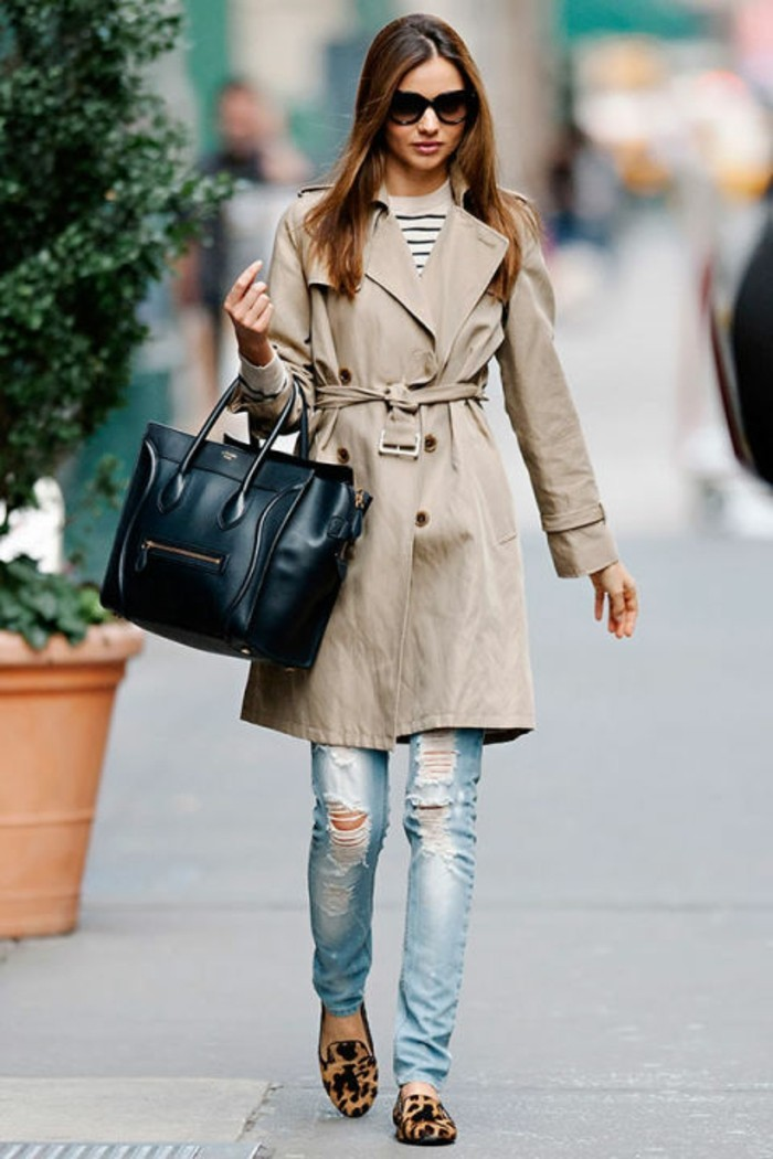 casual business attire, pale beige trench coat, worn over white and black striped top, and ripped distressed pale jeans, by brunette woman with sunglasses, and large black leather bag