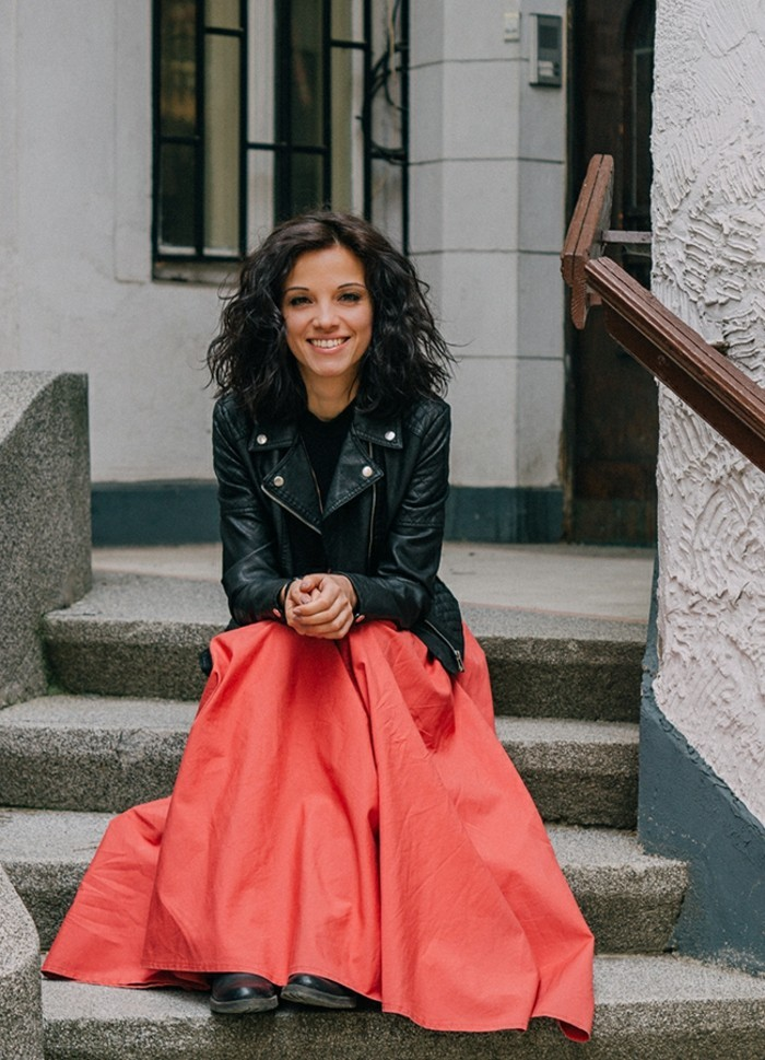 casual clothes, smiling woman with curled brunette hair, sitting on stone steps, and wearing coral red maxi skirt, black top and black leather jacket