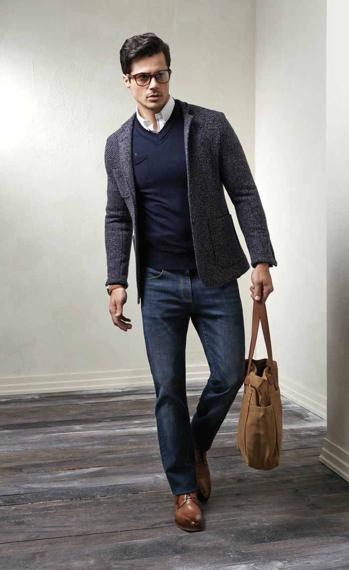 salt and pepper grey blazer, worn over navy v-neck jumper, and white shirt, with business casual jeans, on man with brown shoes, holding a bag in matching color