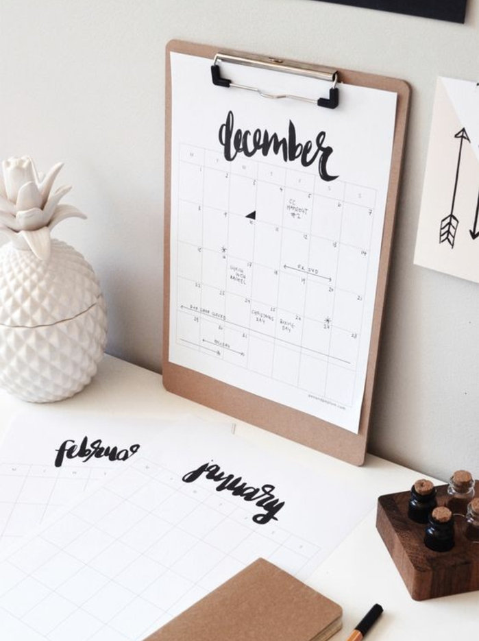beige clip board, with white paper, showing a calendar, with the word december, written in fancy black writing, fun and easy crafts, white desk with stationary
