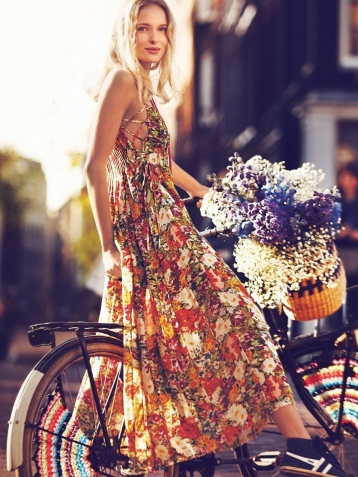 smiling blonde woman, wearing multicolored floral maxi dress, and black and white sneakers, on bike with basket, containing white blue and purple flowers