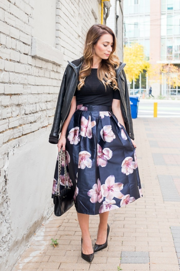 dress attire, shiny dark blue midi skirt, with pale pink flowers, worn with black semi-sheer t-shirt, by woman with honey blonde wavy hair, with black leather jacket over her shoulders