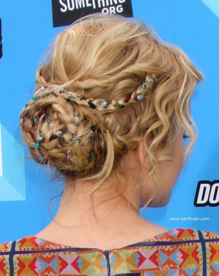 middle age hairstyles, blonde hair with twists and braids, shaped in a bun, with differently colored ribbons woven into it, worn by woman in a patterned top
