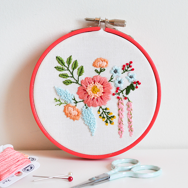 embroidery hoop with white fabric inside, decorated with cross-stitched flowers, art and craft ideas, scissors and pins, pink thread