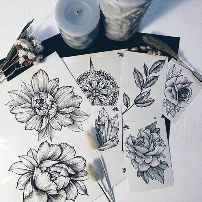 flower tattoo designs, several sheets of white paper, with various tattoo designs, four flowers and a leafy plant, a mandala and a crystal, small dried flowers and candles nearby
