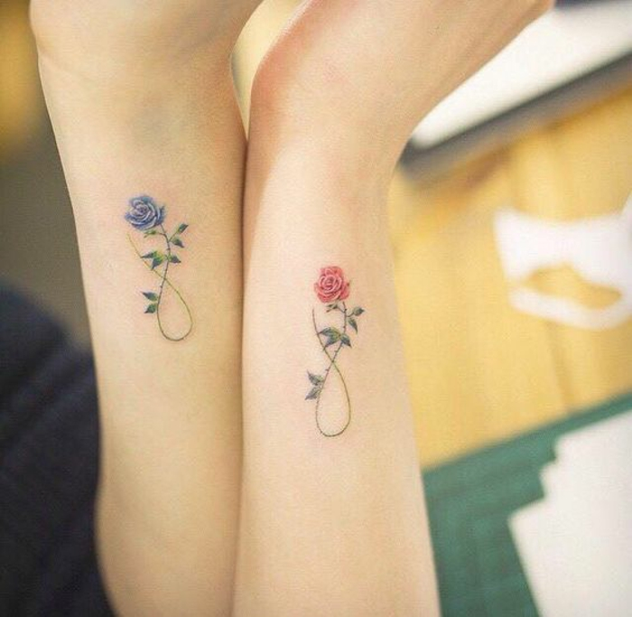 botanical tattoo, two arms with matching rose tattoos, one blue and one red, with identical stalks, twisted to make the sign for infinity