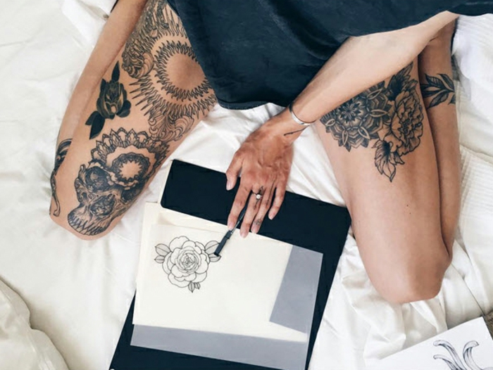 flower tattoos, woman in black top, with various tattoos on her legs, sitting on a bed, holding a pen, near a piece paper, with an outlined drawing of a rose