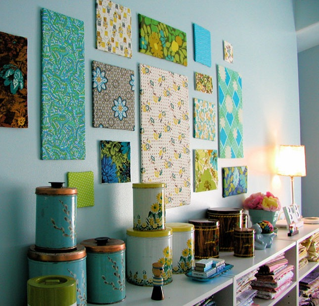 blue wall of a room, with many differently-sized canvases, decorated with various, multicolored patterns, shelf with many different items nearby