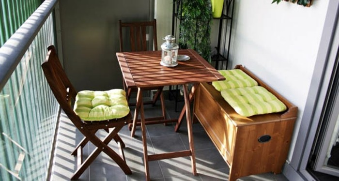 two wooden chairs with table and settee, pale green striped cushions, porch ideas, shelves with plants in background