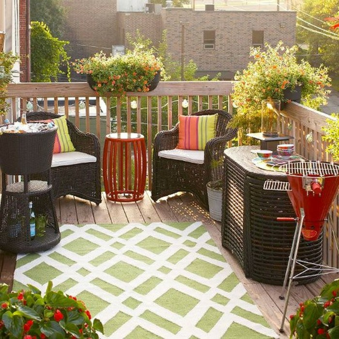 set of brown wicker furniture, two chairs and a table, wine cooler with ice, smaller red metal table, and grill in the same color, outdoor patio ideas, green and white rug and potted plants