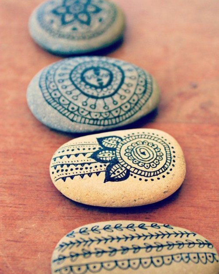 grey stones, decorated with black ink drawings, fun and easy crafts, showing mandalas and leaf patterns