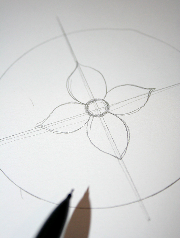 craft ideas, circle drawn in pencil on white piece of paper, with two crossing lines, and a flower in the middle